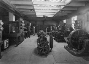 Interior view of the east wing of the Sage Laboratory, depicting students working at some early electrical equipment