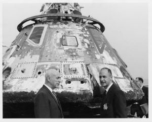 Dr. Robert R. Gilruth and George M. Low in front of Apollo capsule, 1968.
