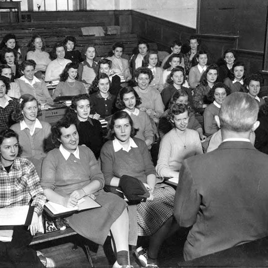 View of women in the Curtiss-Wright program seated in a lecture hall with the instructor's back to the camera.