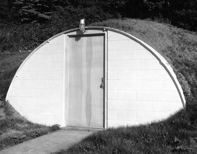 >xterior view of teh entrance to the Seismograph Lab, showing the structure's arched, earth-covered roof (west-southwest elevation, date unknown)