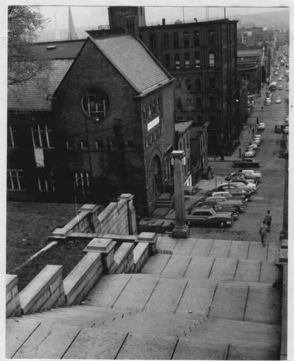 Photograph showing several students walking down the bottom of The Approach steps, with the old gymnasium building, located at the intersection of Broadway and Sixth Street, visible to the left (date unknown, possibly circa 1950s)