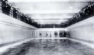 View of the swimming pool located in the basement of the '87 Gym, showing swimmers preparing to compete, and spectators watching from the gallery above