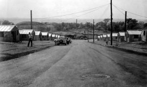 Street-level photograph of the Rendael dormitories, circa late 1940s, depicting dirt road and metal barracks; portion of Houston Field House visible in distance.